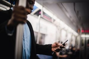 man on train with mobile phone in hand